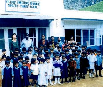 Children at NAWA with school building behind